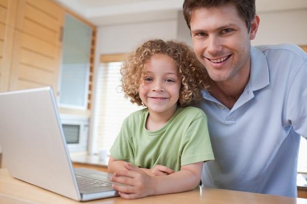 Gelukkige jongen en zijn vader die een notitieboekje gebruiken