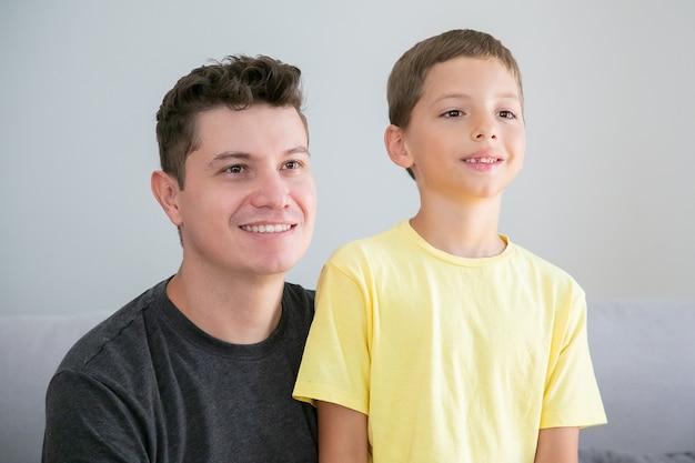Gelukkige jongen en zijn vader zitten samen binnenshuis en wegkijken. gemiddeld schot. familie- en ouderschap concept