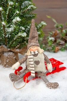 Gelukkige jongen genieten van wintervakantie met slee in de sneeuw. nostalgische kerstachtergrond