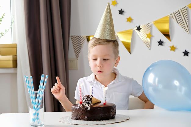 Gelukkige jongen het vieren verjaardag en blazende verlichtingskaarsen op een cake