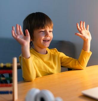 Gelukkige jongen houdt zijn handen in de lucht en neemt online lessen