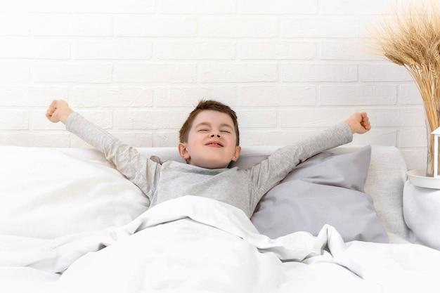 Gelukkige jongen in bed die zijn armen uitstrekt en wakker wordt