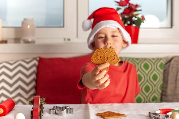 Gelukkige jongen in de hoed van de kerstman die kerstpeperkoek eet en peperkoek voor het nieuwe jaar kookt