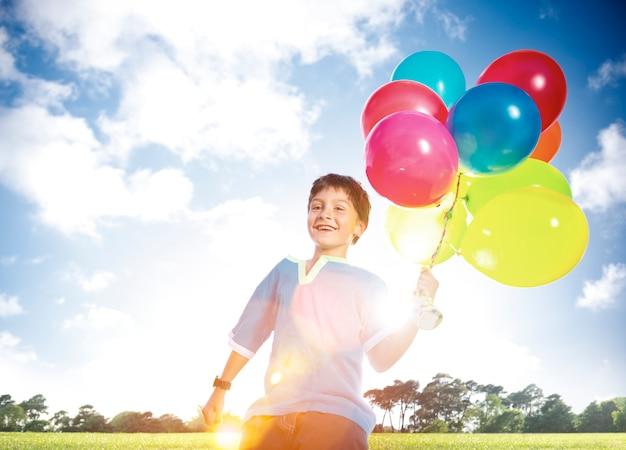 Gelukkige jongen in de open lucht dozijn heliumballonnen speels concept