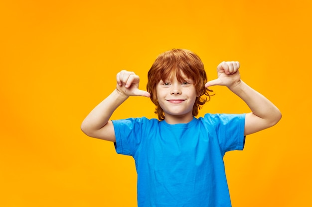 Gelukkige jongen in een blauw t-shirt toont zijn duim en glimlacht
