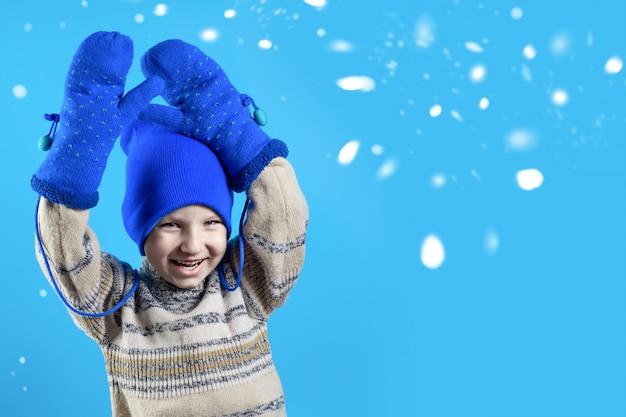 Gelukkige jongen in een blauwe muts, wanten en trui
