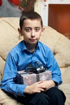 Gelukkige jongen in een comfortabele stoel bij de boom bij de open haard ontving een geschenk.