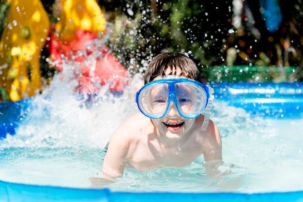 Gelukkige jongen in een onderwatermasker dat in het zwembad zwemt