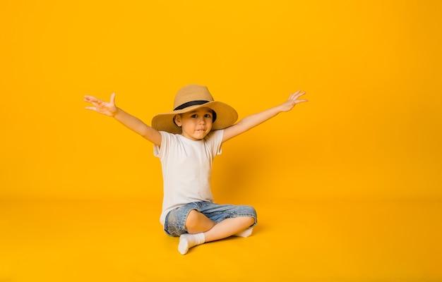 Gelukkige jongen in een strohoed zit op een gele ondergrond en wijst met zijn handen opzij