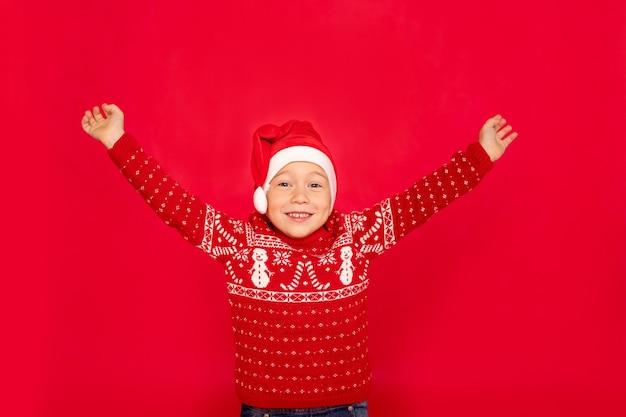 Gelukkige jongen in een sweater en een staande kerstmuts