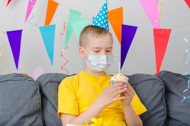 Gelukkige jongen in geneeskunde gezichtsmasker met vakantie cupcake viert verjaardag