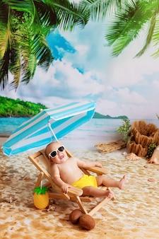 Gelukkige jongen in glazen ligt op een ligstoel, zonnebaadt op een zandstrand met palmbomen aan zee
