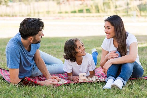 Gelukkige jongen in het park met ouders die van hun tijd genieten