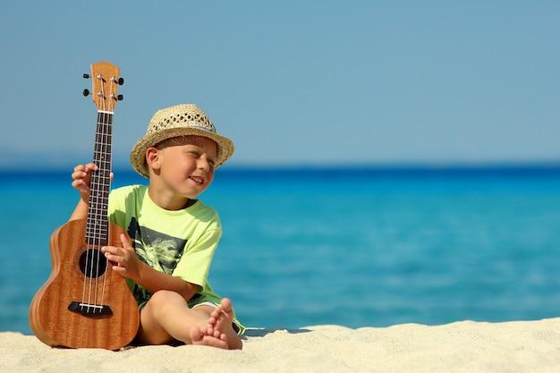 Gelukkige jongen in hoed op het strand aan de blauwe zee met ukelele in de zomer in griekenland