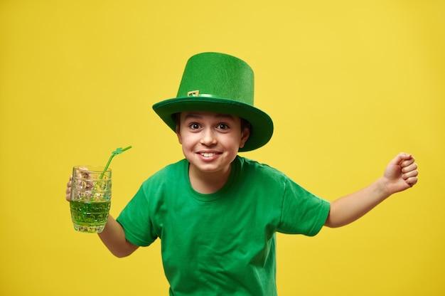 Gelukkige jongen in kabouterhoed met handen omhoog houdt een glas met groene drank vast en drukt geluk uit tijdens het vieren van saint patrick's day