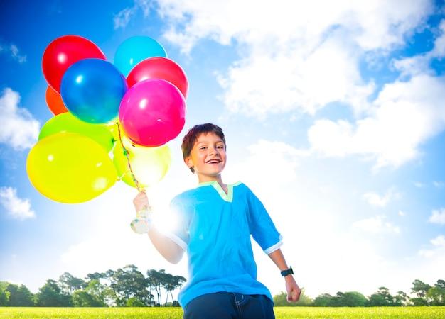 Gelukkige jongen in openlucht met dozijn heliumballons.