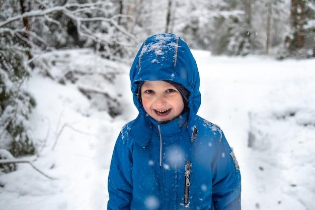 Gelukkige jongen lachen op de achtergrond van het besneeuwde winterbos