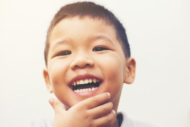 Gelukkige jongen lachen op zoek naar camera portret met isoleren witte ba