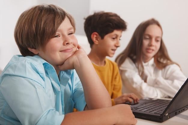 Gelukkige jongen lacht, geniet van studeren op school met zijn vrienden