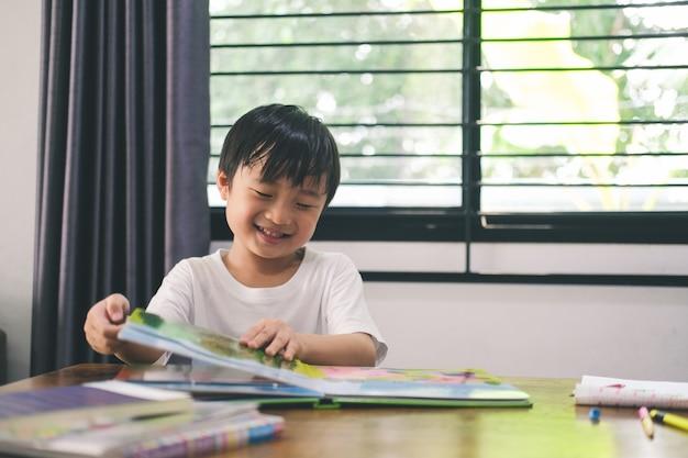 Gelukkige jongen lacht, lacht bij het lezen en leert thuis een prentenboek.