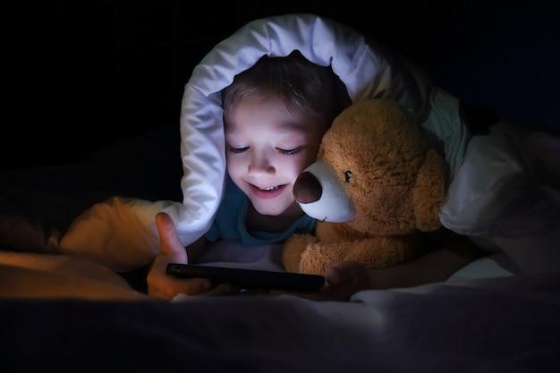 Gelukkige jongen ligt met speelgoed beer in bed onder een deken en met behulp van een digitale tablet-smartphoneapparaat in het donker