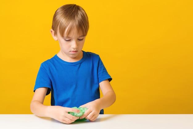 Gelukkige jongen maakt een slijm op de tafel
