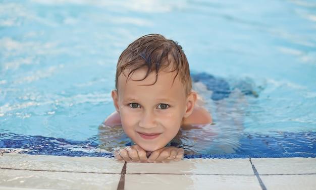 Gelukkige jongen met blonde haar het glimlachen zitting in zwembad