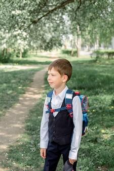Gelukkige jongen met een rugzak en een pet gaat naar school. het begin van het nieuwe schooljaar na de zomervakantie.