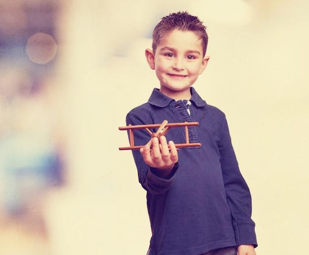 Gelukkige jongen met een vliegtuig op zijn hand
