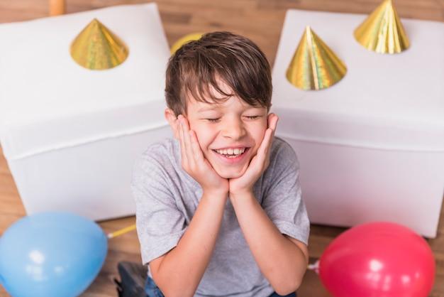 Gelukkige jongen met gesloten ogen het maken van grappig gezicht in partij