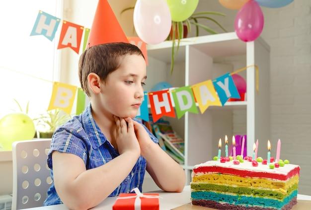 Gelukkige jongen met grappig gezicht dichtbij verjaardagstaart. verjaardagsfeestje en cake