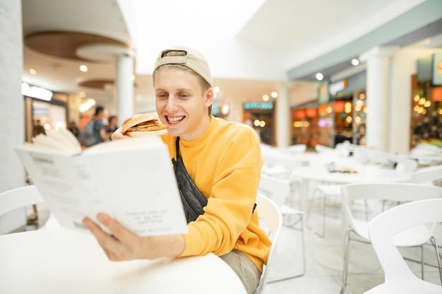 Gelukkige jongen met hamburger in zijn hand zit in een restaurant aan de witte tafel