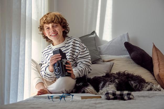 Gelukkige jongen met oude fotocamera en dwergschnauzer binnenshuis