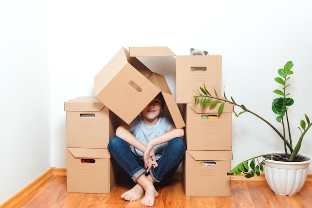 Gelukkige jongen met plezier in het verhuizen van de dag naar een nieuw huis. familie verhuist naar een nieuw appartement