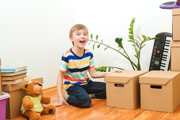 Gelukkige jongen met plezier in het verhuizen van de dag naar een nieuw huis. huisvesting van een jong gezin met een kind. familie verhuist naar een nieuw appartement.