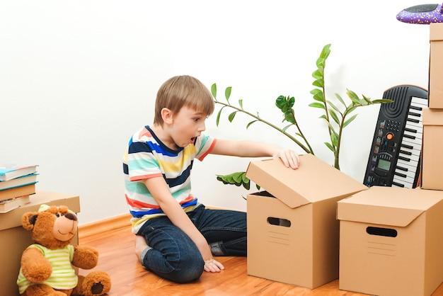 Gelukkige jongen met plezier in het verhuizen van de dag naar een nieuw huis. huisvesting van een jong gezin met een kind.