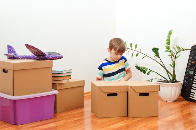 Gelukkige jongen met plezier in het verhuizen van de dag naar een nieuw huis.