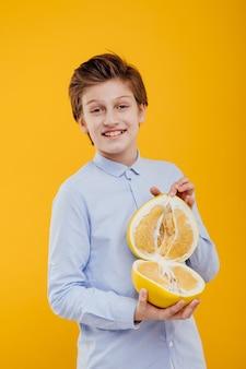 Gelukkige jongen met pompelmoesfruit in hand, exotisch fruit, banaan en sinaasappel, in het blauwe overhemd, dat op gele muur wordt geïsoleerd