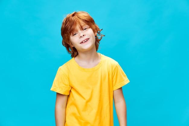 Gelukkige jongen met rood haar glimlachend en kantelde zijn hoofd opzij