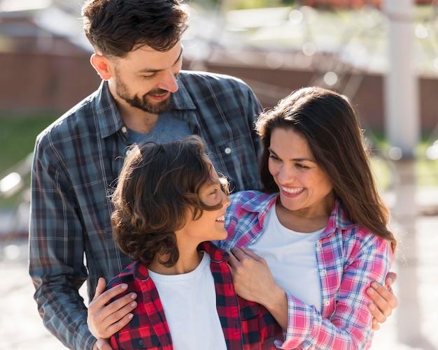 Gelukkige jongen met zijn ouders die van hun tijd buiten genieten