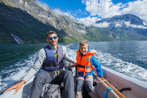 Gelukkige jongen met zijn vader die de motorboot drijft