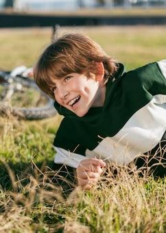 Gelukkige jongen ontspannen op gras tijdens het rijden met zijn fiets