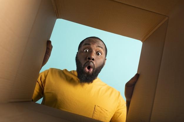 Gelukkige jongen ontvangt een pakket van online winkelbestelling. blije en verbaasde uitdrukking. blauwe muur.
