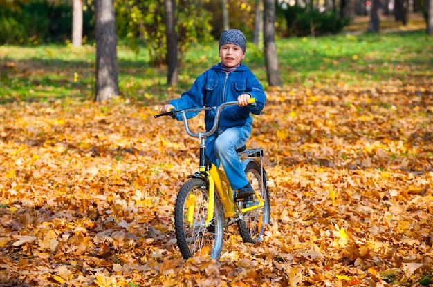 Gelukkige jongen rijdt op een fiets in de herfstpark