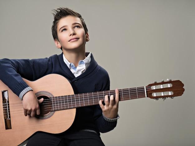 Gelukkige jongen speelt met plezier op akoestische gitaar.