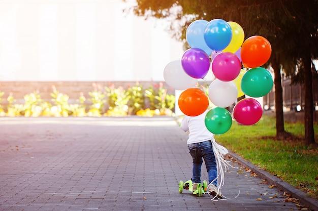 Gelukkige jongen spelen met een bos van ballonnen buiten en een scooter rijden.