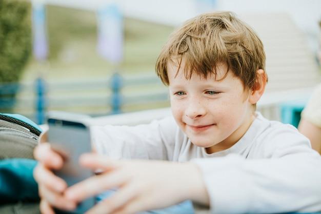 Gelukkige jongen spelen op een mobiele telefoon