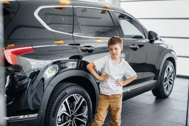 Gelukkige jongen staat in de buurt van een nieuwe auto voordat hij hem koopt
