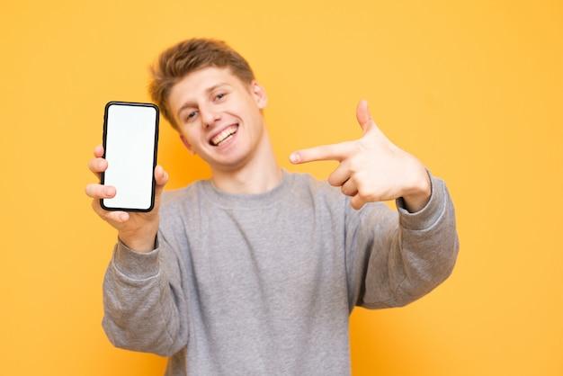 Gelukkige jongen staat op een gele achtergrond, kijkt in de camera en toont de vingers op de smartphone in de hand houdt
