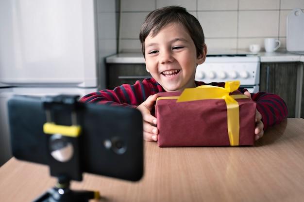 Gelukkige jongen thuis bedankt iemand telefonisch via een videoconferentie voor het geschenk dat hij heeft ontvangen.